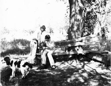 Aldo Leopold and Luna sharpening shovel at the shack