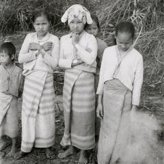 Three White Lahu (Lahu Hpu) girls stand in a village southwest of Muang Meung in Houa Khong Province