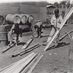 Boys split bamboo to weave matting to be used on walls of structures in Attapu Province