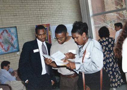 Students read program at 1995 graduation reception