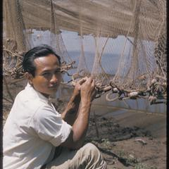 Young man fixing fish net