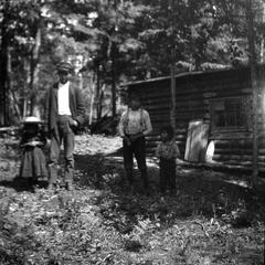 Unidentified man and children near cabin