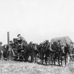 Soldiers of the US Army's 15th Infantry Regiment unloading cargo from horse-drawn cart.