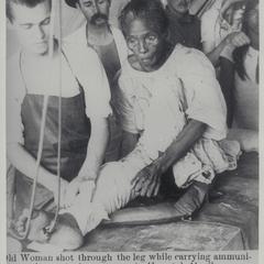 Elderly woman receiving treatment for a gunshot wound in the leg received when aiding insurgents, Manila, 1899