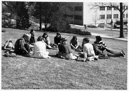 Students sitting on the lawn of the home economics building