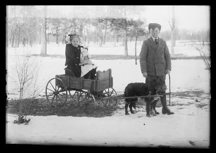 Children with dog pulling wagon