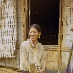 A Nyaheun woman is seated on the porch of her dwelling in Attapu Province