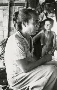 A White Lahu (Lahu Hpu) man is seated on the porch of his home in Houa Khong Province