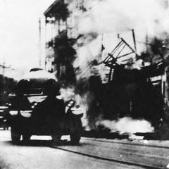Japanese armored vehicles rolling along ruined city street.