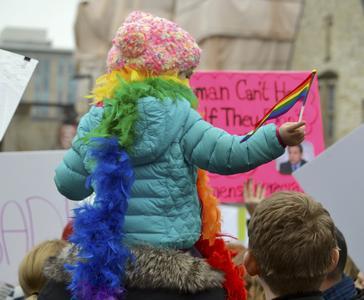 Kid waiving rainbow flag on shoulders