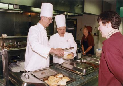 Chancellor Mark L. Perkins serving food in cafeteria line