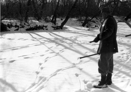 """Carrying saw in the """"Shack Slough,"""" ca. 1936, snow scene with tracks"""
