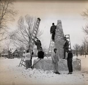 Students with ladders building a snow sculpture