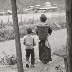 White Hmong woman and son walk near an airstrip in northern Laos.
