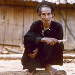 A Yao (Iu Mien) man crouches on a log in his village of Houei Lai in Houa Khong Province