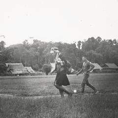 Akha woman and soldier walking across air strip at Muang Meung in Houa Khong Province