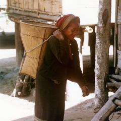 A Khmu' woman carries a basket on her back in her village in Houa Khong Province