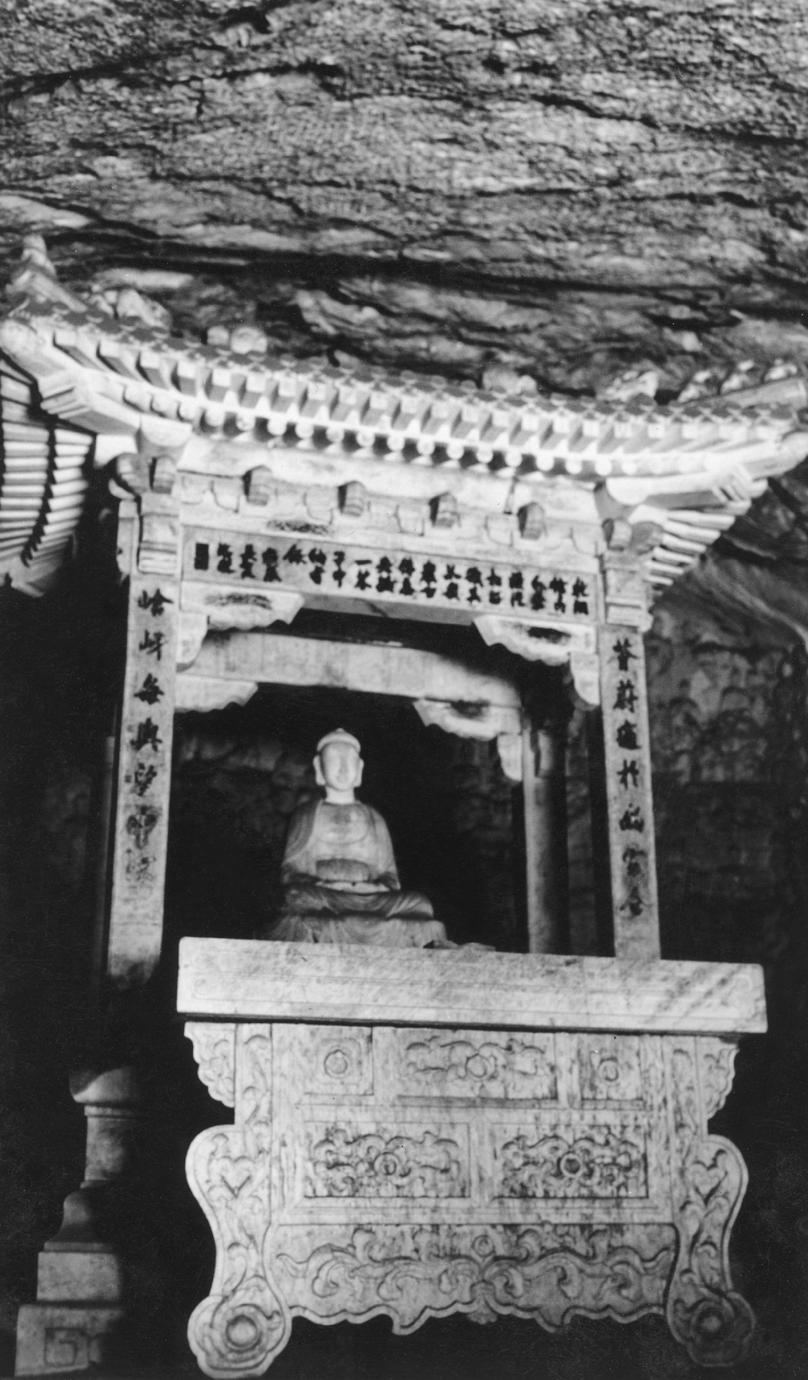 Buddha statue in a carved stone shrine inside a cave.