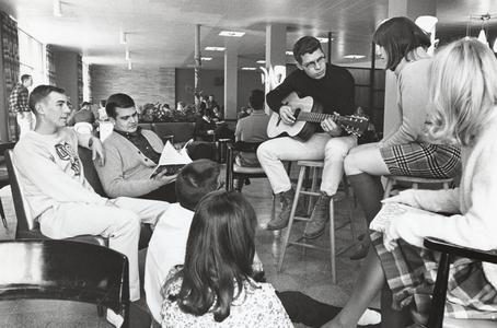 Student plays the guitar for friends