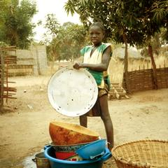 Young Girl Washing Dishes in Typical Fashion in Goudomp