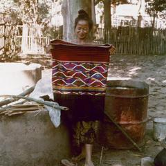 Kalom woman displays a newly woven skirt in Houa Khong Province