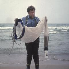 Larry Crowder standing with plankton net on a Lake Michigan beach
