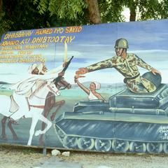 Political Sign with Past Soldiers Passing Weapons to Today's