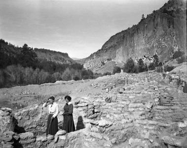 Women walking among ruins at Frijoles Canyon