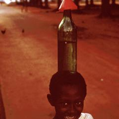 Young Girl Carrying Bottle on Her Head