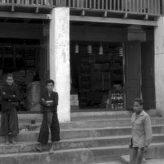 Akha tribesmen on steps of Chinese shops