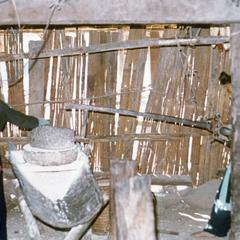 Milling rice inside the home of a White Hmong family in Houa Khong Province