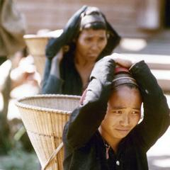 Two Khmu' women carry baskets strapped to their foreheads in Houa Khong Province