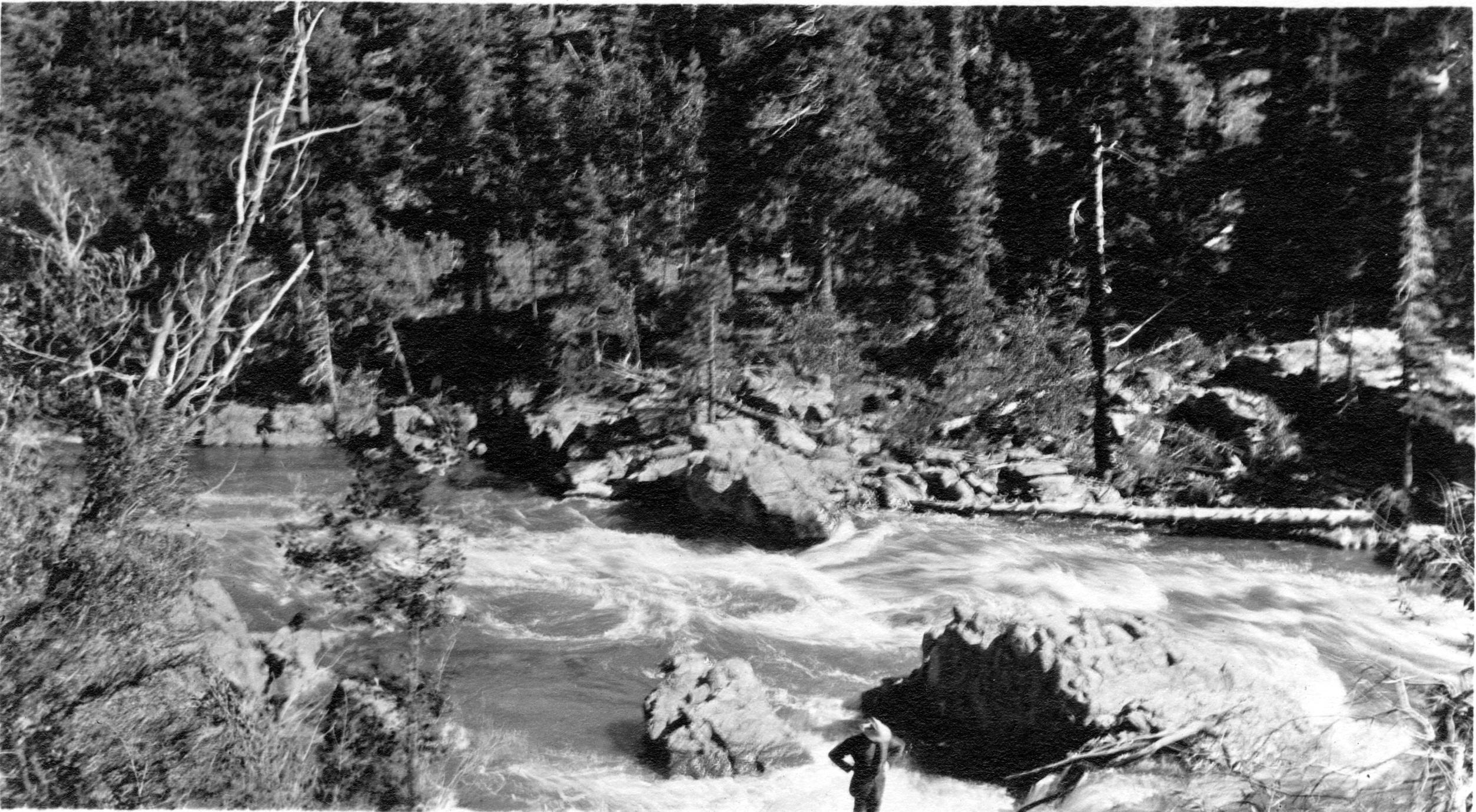 Man standing at river rapids