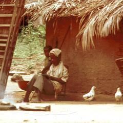 Elderly Man Resting Beside House and Bed