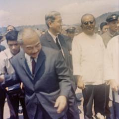 Prince Souphanouvong walks through the crowds with Phoumi Vongvichit and Pheng Phongsavan at the Luang Prabang airport