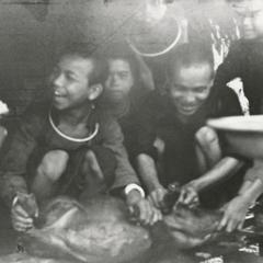 Akha youth slaughtering a pig at the village of Phate in Houa Khong Province