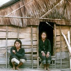 Two Khmu' women are seated in front of their house in Houa Khong Province