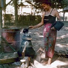 A Kalom woman makes rice whiskey next to her house in Houa Khong province