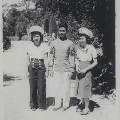 A cadet and two girls in cadet caps, Baguio