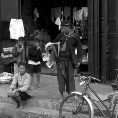 Yao (?) tribal mountaineer with purchase of woven goods, woman with Lao skirt sitting on steps in front of store which apparently features bolts of clothing and enamelware