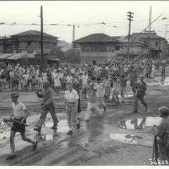Filipino crowds throng as soldiers pass with wounded Japanese in tow, Manila, 1945