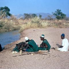 Fulbe Men Resting and Getting Haircut by River