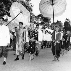 After ceremony, newlyweds walk through main street of town, shaded by white silk royal umbrellas held by Kammu (Khmu') honor guards