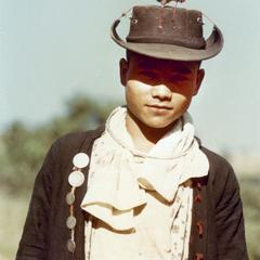An Akha young man poses in traditional shirt and untraditional hat in Houa Khong Province