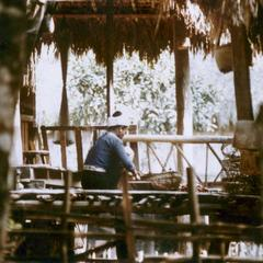 Woman working on the porch of her home in the Lu village of Ta Fa in Houa Khong Province