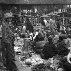 Soldiers looking over seated Lao women vegetable vendors