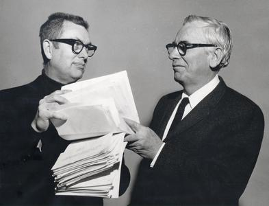 Edwin Young receives a petition from professor Reid Bryson