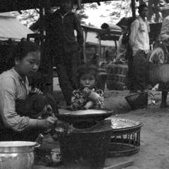 Lao woman with child preparing food for sale